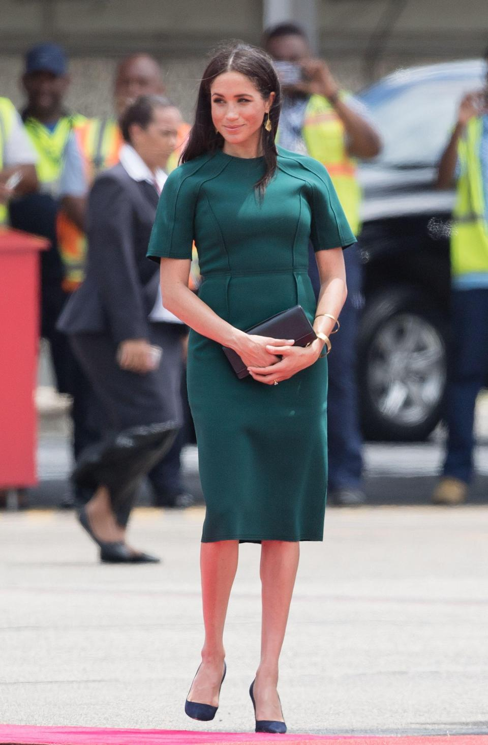 """<p>In Western Fiji Markle was dressed in a forest green shift dress by Canadian fashion designer <a href=""""https://www.net-a-porter.com/us/en/Shop/Designers/Jason_Wu?pn=1&npp=60&image_view=product&dScroll=0"""" rel=""""nofollow noopener"""" target=""""_blank"""" data-ylk=""""slk:Jason Wu"""" class=""""link rapid-noclick-resp"""">Jason Wu</a>, the mother-to-be accessorised her look with black suede <a href=""""https://www.google.co.uk/aclk?sa=L&ai=DChcSEwj7mr_lmqHeAhWD4ncKHT7ECwkYABAPGgJlZg&sig=AOD64_0XSyNrPO_fC8Sx9w_NQ5J87WYxig&ctype=5&ved=0ahUKEwjX4bflmqHeAhVSJ1AKHRAXBT8Qww8IcA"""" rel=""""nofollow noopener"""" target=""""_blank"""" data-ylk=""""slk:Manolo Blank BB pumps"""" class=""""link rapid-noclick-resp"""">Manolo Blank BB pumps</a> and a pair of statement gold drop earrings.</p>"""