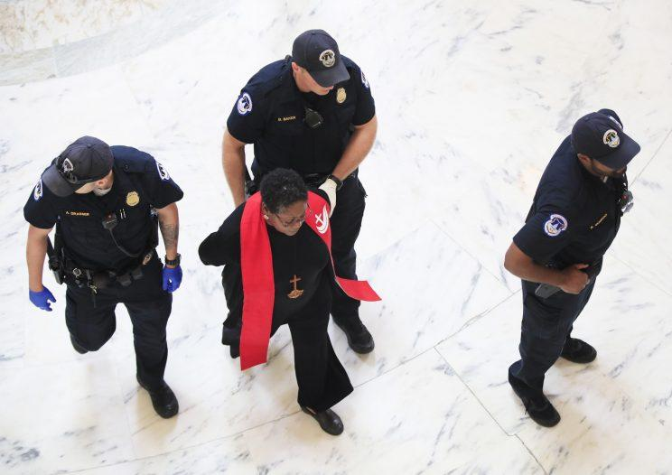 A minister belonging to a group demanding that Congress to reject the Trump administration's budget proposals and health care bill is arrested during a demonstration in the Russell Senate Building on Capitol Hill in Washington on July 18, 2017. (Photo: Manuel Balce Ceneta/AP)