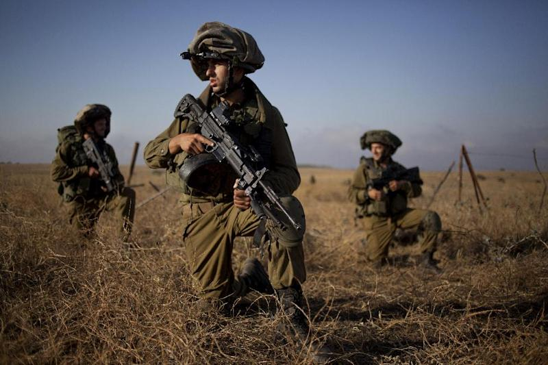 Israeli soldiers of the Golani brigade take position during training in the Israeli controlled Golan Heights near the border with Syria Wednesday, June 26, 2013. (AP Photo/Ariel Schalit)