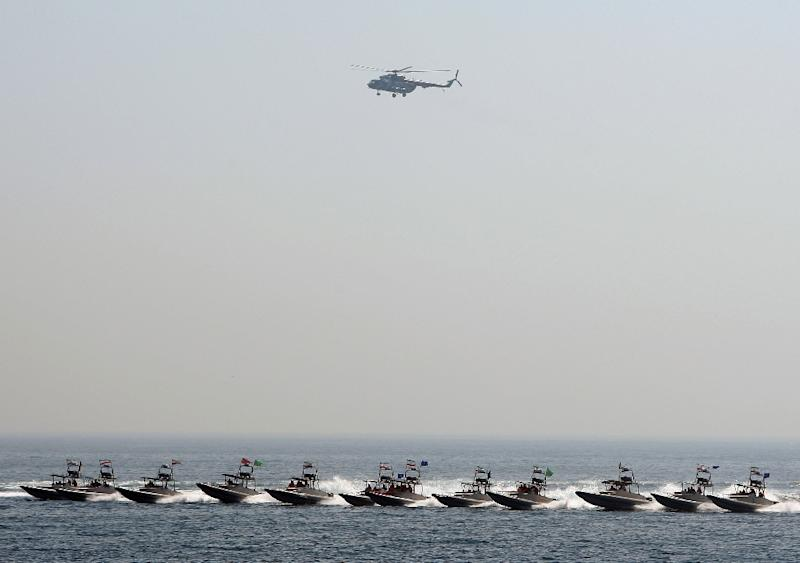 An Iranian military helicopter flies over Revolutionary Guards' fast boats during naval exercises in the Gulf in 2010