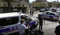 In this image made from video, police near the scene of a stabbing at a police station in Rambouillet, southwest of Paris, Friday, April 23, 2021. Authorities say a French policewoman has been stabbed to death inside her police station and that fellow officers nearby shot and killed the suspected attacker. The identity and the motive of the assailant were not immediately clear. (Clement Lanot via AP)
