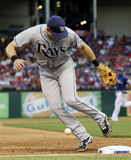 Tampa Bay Rays third baseman Evan Longoria watches a ball hit by Texas Rangers' Michael Young bounce over the bag and stay fair in the first inning of a baseball game, Friday, April 27, 2012, in Arlington, Texas. Young was safe at first on the hit. (AP Photo/Tony Gutierrez)