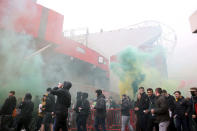 Fans make their way past barriers outside the ground as they let off flares whilst protesting against the Glazer family, owners of Manchester United, before their Premier League match against Liverpool at Old Trafford, Manchester, England, Sunday, May 2, 2021. (Barrington Coombs/PA via AP)