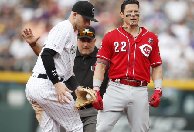 Cincinnati Reds' Derek Dietrich, right, ends up with his chain on his chin after reaching second base on a double as Colorado Rockies shortstop Trevor Story, left, applies a late tag in the second inning of a baseball game Sunday, July 14, 2019, in Denver.(AP Photo/David Zalubowski)