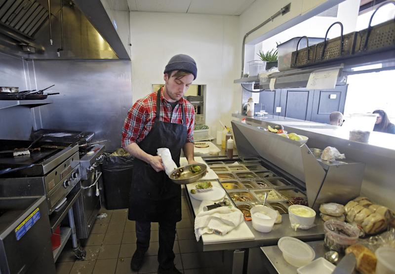 In this Tuesday, Jan. 28, 2014 photo, cook Joe Egar plates an order at Bonbon Pastry and Cafe in Cleveland. Single-digit temperatures across the U.S. and record snowfalls in the Midwest since the beginning of January have put the freeze on businesses that rely on walk-ins and appointments. At the cafe in the city's Market Square district, this past weekend was especially slow with whiteout conditions making going outside unappealing for customers. (AP Photo)