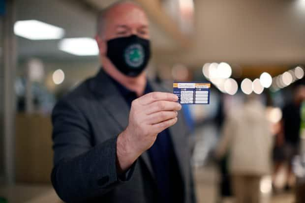B.C. Premier John Horgan shows his vaccination card after receiving a dose of the AstraZeneca-Oxford vaccine at the pharmacy in James Bay Thrifty's Foods in Victoria on Friday. (Chad Hipolito/Canadian Press - image credit)