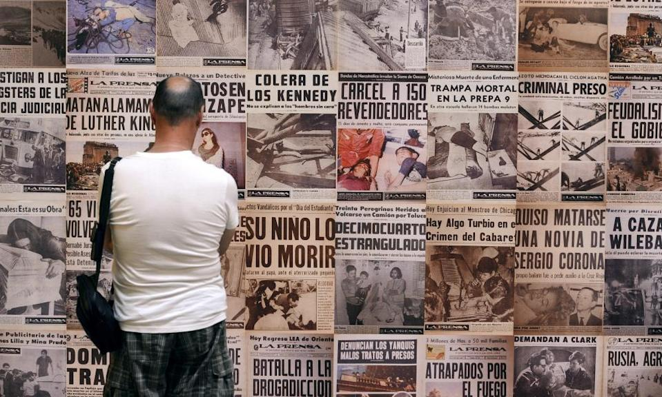 A visitor looks at newspaper covers made by Mexican photographer Enrique Metinides at an exhibition.