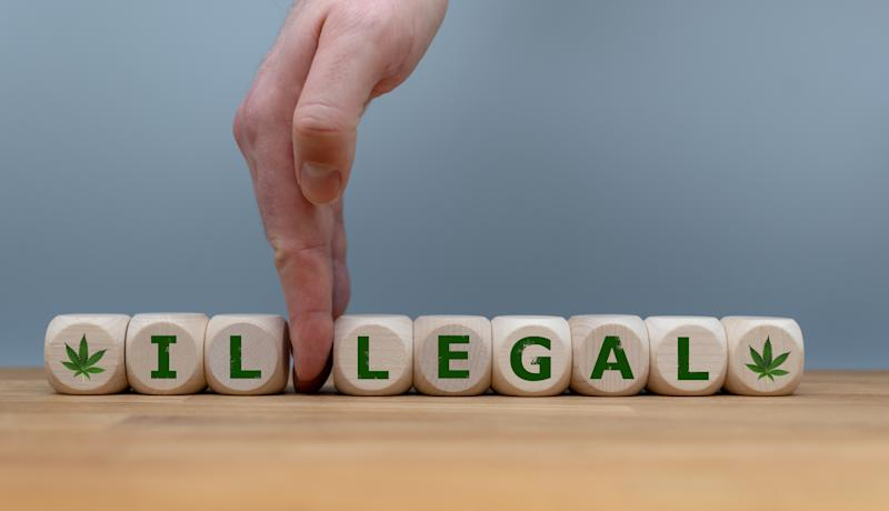 """Wooden cubes lined up spelling out """"Illegal"""" with cubes showing marijuana leaves at both ends and a hand in between the two blocks with the letter """"l."""""""