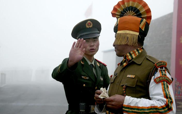 A Chinese border guard, standing next to his Indian counterpart, attempts to block a photographer from taking photos - Diptendu Dutta/AFP