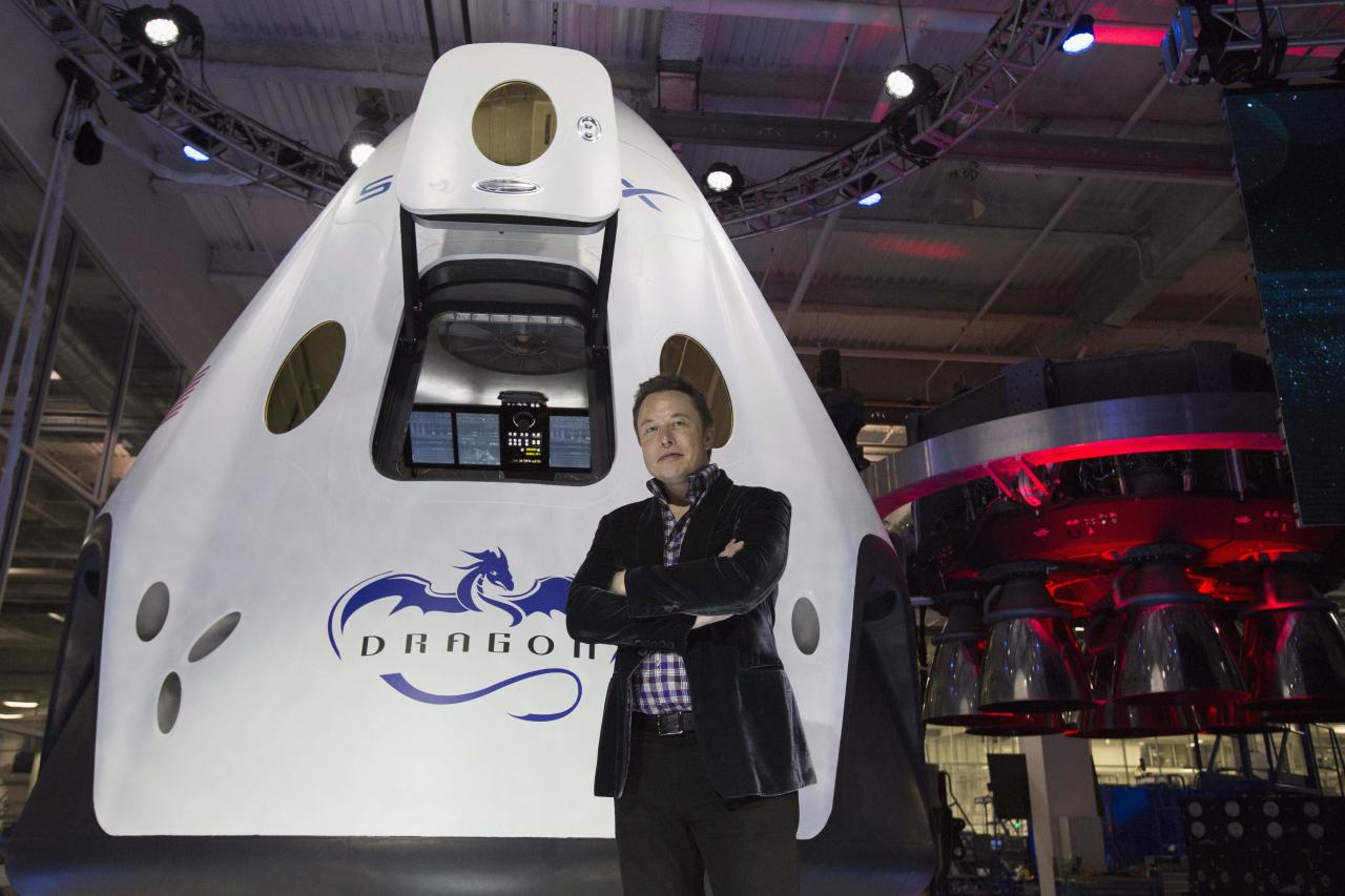 SpaceX CEO Elon Musk poses by the Dragon V2 spacecraft after it was unveiled in Hawthorne, California May 29, 2014. Space Exploration Technologies, or SpaceX, on Thursday unveiled an upgraded passenger version of the Dragon cargo ship NASA buys for resupply runs to the International Space Station. REUTERS/Mario Anzuoni (UNITED STATES - Tags: POLITICS TRANSPORT SCIENCE TECHNOLOGY SOCIETY)