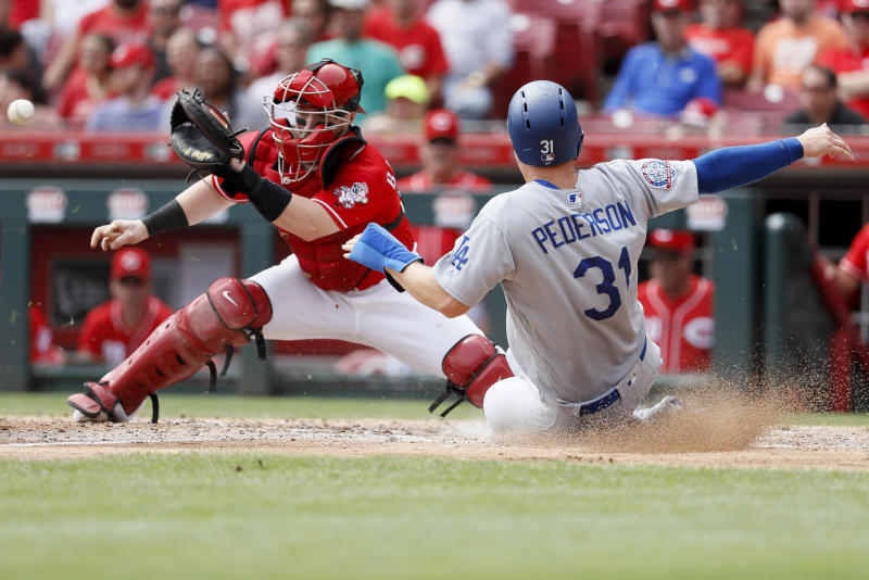 Los Angeles Dodgers' Joc Pederson scores against Cincinnati Reds catcher Tucker Barnhart, left, in the fifth inning of a baseball game, Wednesday, Sept. 12, 2018, in Cincinnati. (AP Photo/John Minchillo)