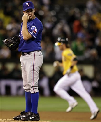 Texas Rangers pitcher Roy Oswalt, left, waits for Oakland Athletics' Josh Reddick to run the bases after hitting a home run in the seventh inning of a baseball game, Tuesday, July 17, 2012, in Oakland, Calif. (AP Photo/Ben Margot)