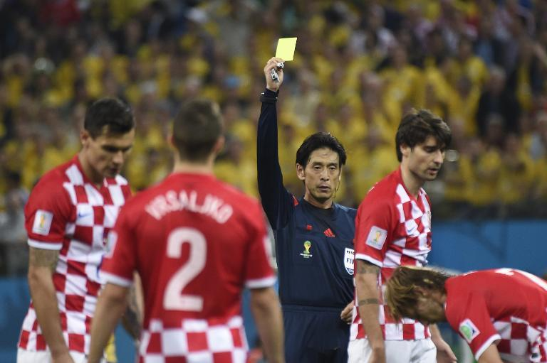 Japanese referee Yuichi Nishimura (C) gives a yellow card to Croatia's Vedran Corluka (R) during their World Cup opening match against Brazil at the Corinthians Arena in Sao Paulo on June 12, 2014