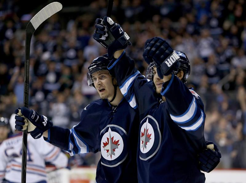 Winnipeg Jets' Mark Scheifele (55) and Michael Frolik (67) celebrate after Frolik scored against the Edmonton Oilers during the second period of a preseason NHL hockey game in Winnipeg, Manitoba, Tuesday, Sept. 17, 2013. (AP Photo/The Canadian Press, Trevor Hagan)