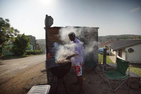 A man cooks Chicken Dust on a street corner barbecue in KwaMashu, South Africa in an undated photo. Courtesy Matthew Salleh/Handout via REUTERS