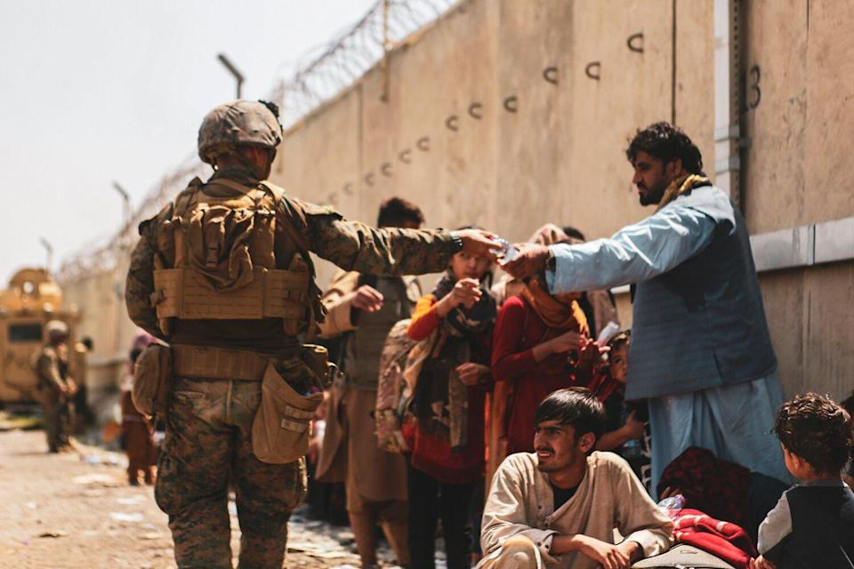 HAMID KARZAI INTERNATIONAL AIRPORT, AFGHANISTAN - AUGUST 22: This handout image shows A Marine with the 24th Marine Expeditionary unit (MEU) passes out water to evacuees during an evacuation at Hamid Karzai International Airport, Kabul, Afghanistan, Aug. 22. U.S. service members are assisting the Department of State with a Non-combatant Evacuation Operation (NEO) in Afghanistan.