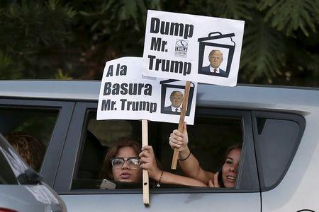 Women hold protest signs as they drive past the Luxe Hotel, where Republican presidential candidate Donald Trump was expected to speak in Brentwood, Los Angeles, California, United States July 10, 2015. REUTERS/Lucy Nicholson