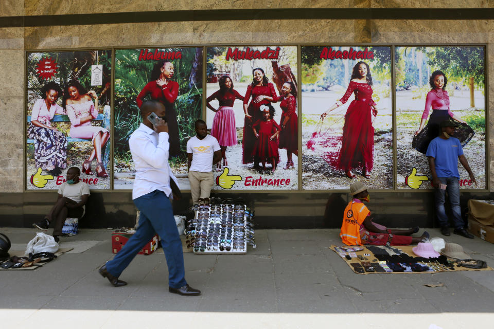 A man chats on the phone while walking past vendors selling various items on the streets of Harare, Tuesday, Sept. 22, 2020. As Zimbabwe's coronavirus infections decline, strict lockdowns designed to curb the disease are being replaced by a return to relatively normal life. The threat has eased so much that many people see no need to be cautious, which has invited complacency. (AP Photo/Tsvangirayi Mukwazhi)