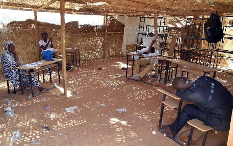 Workers of electoral commission wait for people to come to cast their ballot at a polling station in Niamey on March 20, 2016 during the second round of the presidential election (AFP Photo/Issouf Sanogo)