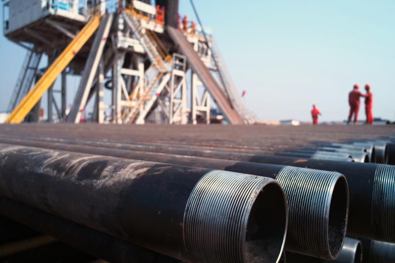 A stack of drilling pipe near a rig.
