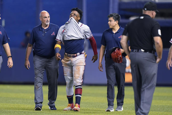 Atlanta Braves right fielder Ronald Acuna Jr., center, attempts to walk after trying to make a catch on an inside-the-park home run hit by Miami Marlins' Jazz Chisholm Jr. during the fifth inning of a baseball game, Saturday, July 10, 2021, in Miami. Aunca left the game. (AP Photo/Lynne Sladky)