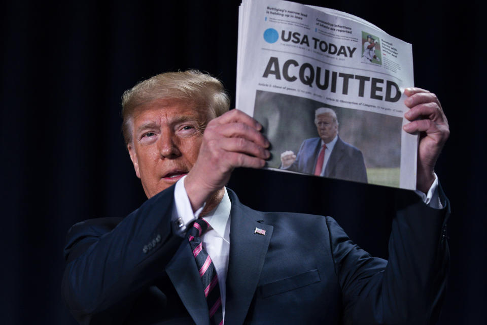 """FILE - In this Feb. 6, 2020, file photo, President Donald Trump holds up a newspaper with the headline that reads """"ACQUITTED"""" at the 68th annual National Prayer Breakfast, at the Washington Hilton in Washington. (AP Photo/ Evan Vucci, File)"""
