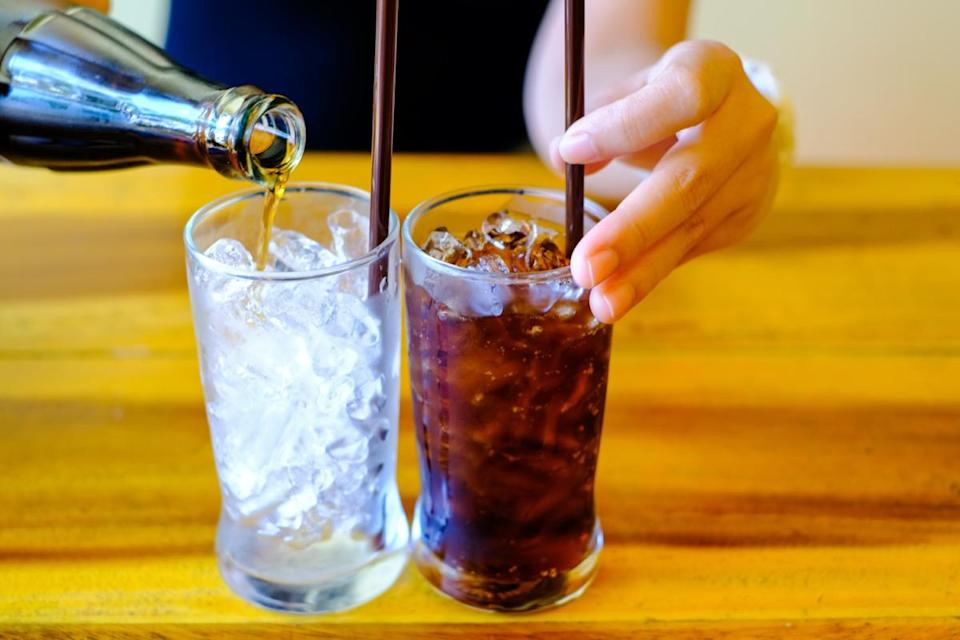 Woman hand giving one glass of Soft drinks with ice. and one Glass with ice in glass ready to refresh you