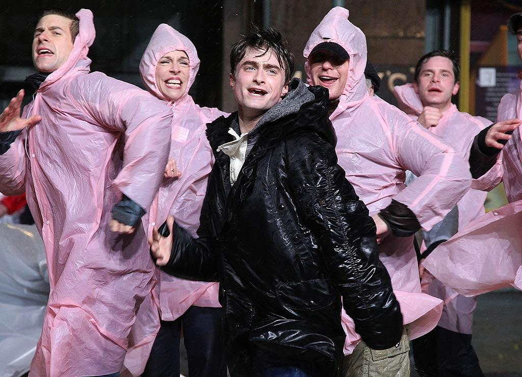 """""""Harry Potter"""" star Daniel Radcliffe was singin' in the rain on Tuesday, when he and the rest of the cast of the Broadway musical """"How to Succeed in Business Without Really Trying"""" rehearsed for the 85th annual Macy's Thanksgiving Day parade in New York. Let's hope Thanksgiving brings better weather! (11/22/2011)"""