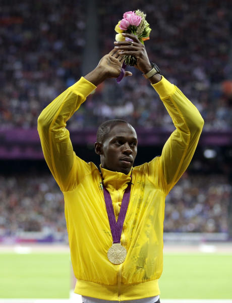 Jamaica's Usain Bolt gestures on the podium after receiving his gold medal for the men's 100-meters during the athletics in the Olympic Stadium at the 2012 Summer Olympics, London, Monday, Aug. 6, 2012. (AP Photo/Matt Slocum)