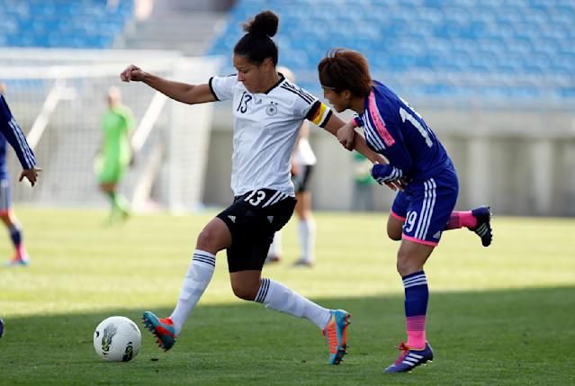 Germany's Celia Sasic, left, battles for the ball with Japan's Ariyoshi Saori during the women's soccer Algarve Cup final match between Germany and Japan at the Algarve stadium, outside Faro, southern Portugal, Wednesday, March 12, 2014. (AP Photo/Francisco Seco)