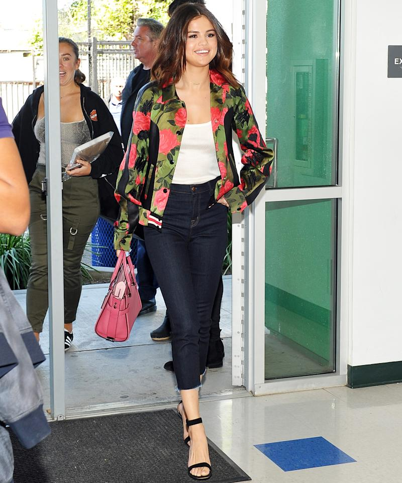 "<p>Gomez <a rel=""nofollow"" href=""http://www.instyle.com/news/selena-gomez-coach-surprise-high-school-students"">surprised high schoolers</a>, with help from Coach and the charity Step Up, and discussed female empowerment with the young students. She looked casual and cool in a pair of dark wash, cropped jeans, a white tank, and a floral jacket (try a similar rose-print bomber <a rel=""nofollow"" href=""https://click.linksynergy.com/fs-bin/click?id=93xLBvPhAeE&subid=0&offerid=465536.1&type=10&tmpid=2425&RD_PARM1=https%3A%2F%2Fwww.bloomingdales.com%2Fshop%2Fproduct%2Fjoes-jeans-the-elsie-floral-printed-bomber-jacket%3FID%3D1845860%2526CategoryID%3D1001521%2526LinkType%3D&u1=ISSelenaGomezStreetStyle3.24JA"">here</a>).</p>"
