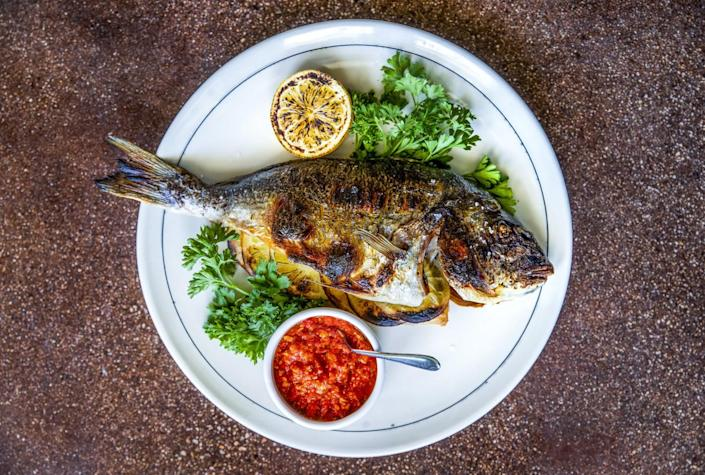 A whole roasted fish with a bowl of romesco sauce on the side.
