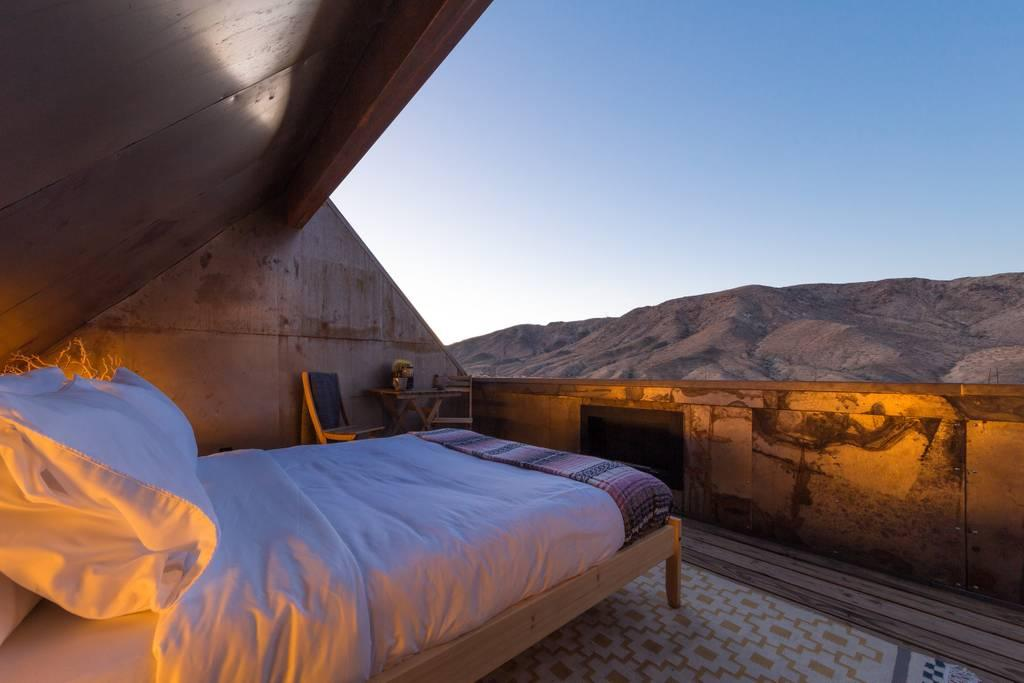 """<p>This super chic Airbnb Plus designed by L.A.-based architect Malek Alqadi has an outdoor bedroom built for taking in the Milky Way. On two and a half acres, the two-bedroom home (plus the outdoor loft) is just far enough from civilization to provide a dark-enough sky, while still close enough to offer plenty of activities—<a href=""""https://www.cntraveler.com/activities/joshua-tree/joshua-tree-national-park?mbid=synd_yahoo_rss"""" target=""""_blank"""">Joshua Tree National Park</a> is a short eight-minute drive away. (Joshua Tree was <a href=""""https://www.cntraveler.com/story/joshua-tree-national-park-to-get-dark-sky-park-designation-for-stargazing?mbid=synd_yahoo_rss"""" target=""""_blank"""">recognized as a dark sky park</a>, one step down from reserve, in 2017, too.) Plus, the home comes with modern amenities like Wi-Fi and air conditioning. While the outdoor bedroom, reclaimed steel exterior, and modern industrial interiors offer plenty of Instagram fodder, we're eyeing the <a href=""""https://www.instagram.com/p/BjlwV9YFnBY/?hl=en&taken-by=folly.folly"""" target=""""_blank"""">outdoor soaking tub</a>, made out of what's essentially a metal trough. In case you need a reminder, the Airbnb listing comes with a clear disclaimer: """"If you are by no means an outdoors person, this cabin will not be a good fit for you.""""</p> <p><strong>Book Now:</strong> <a href=""""https://airbnb.pvxt.net/oDdyg"""" rel=""""nofollow"""" target=""""_blank""""><strong>F</strong>rom $225 per night, airbnb.com</a></p>"""