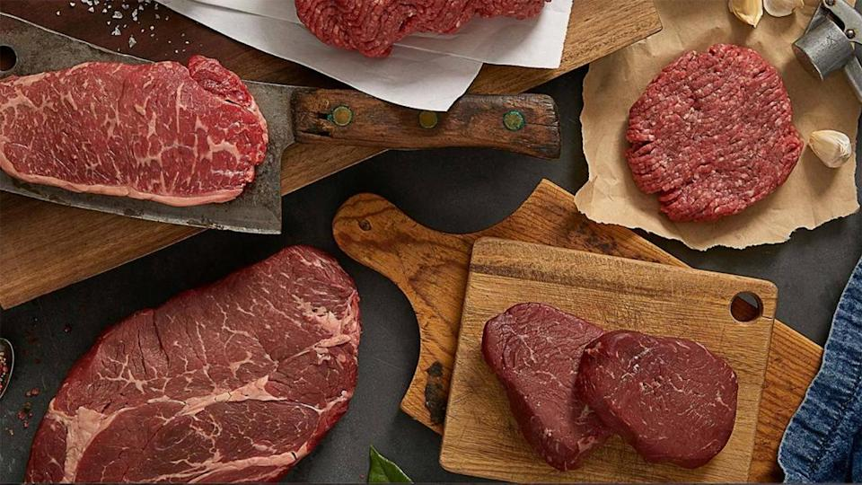 four pieces of raw meat along with knives and cutting boards