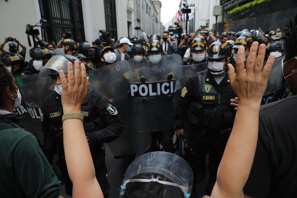 Police block supporters of former President Martín Vizcarra protesting near Congress while lawmakers swear-in Manuel Merino, head of Peru's legislature, as the new president in Lima, Peru, Tuesday, Nov. 10, 2020. Congress voted to oust Vizcarra over his handling of the new coronavirus pandemic and unproven allegations of corruption years ago. (AP Photo/Rodrigo Abd)