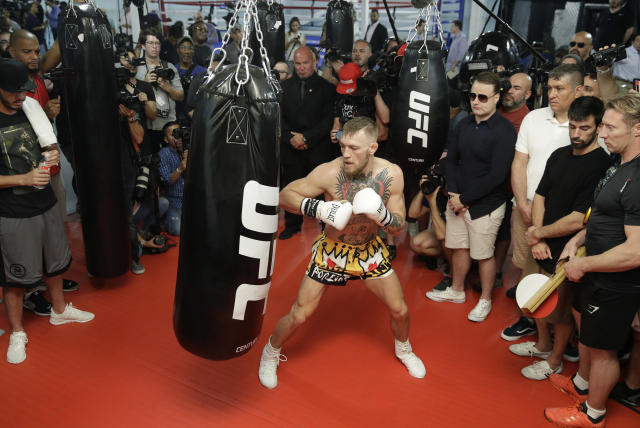 Conor McGregor hits a heavy bag while surrounded by media and supporters during a workout on Aug. 11. (AP)