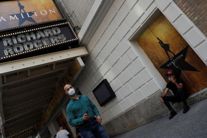 """A man walks wearing a protective face mask past the marquee for the Broadway show """"Hamilton"""" in the Times Square area of Manhattan, New York City"""