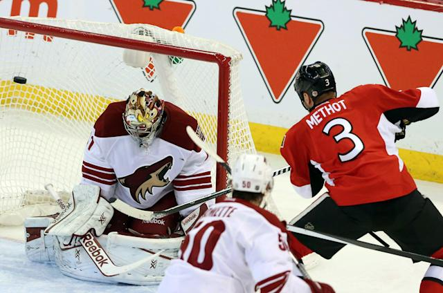 Ottawa Senators Marc Methot (3) fires the puck past Phoenix Coyotes goaltender Mike Smith (41) during second period action of an NHL hockey match in Ottawa, Canada, on Saturday, Dec. 21, 2013. (AP Photo/The Canadian Press, Fred Chartrand)