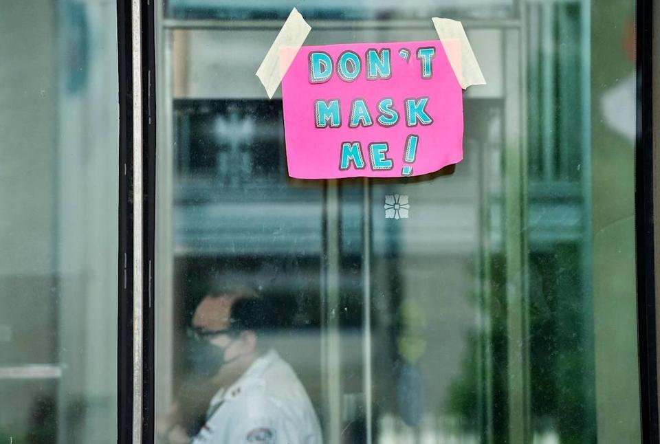 A security guard works near the entrance to City Hall. About 50 people protested the mask mandate on the north side of Kansas City's city hall and taped a sign up at the entrance Thursday, Aug. 5, 2021. The mandatory mask order went into effect on Monday.
