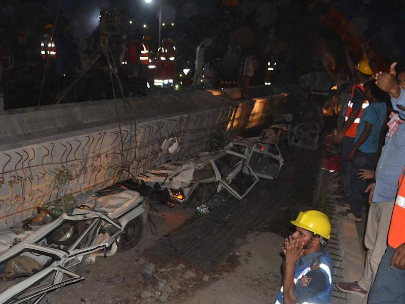 Rescue workers prepare to remove a beam as vehicles are seen trapped under the rubble after a part of an under construction flyover collapsed in Varanasi, India (REUTERS/Stringer)