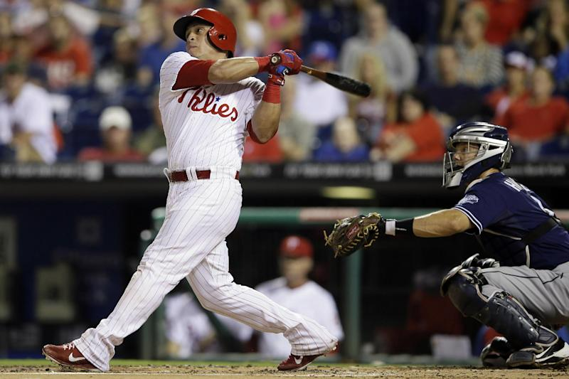 Philadelphia Phillies' Carlos Ruiz, left, follows through after hitting a two-run double during the first inning of a baseball game against San Diego Padres, Thursday, Sept. 12, 2013, in Philadelphia. At right is Nick Hundley. (AP Photo/Matt Slocum)