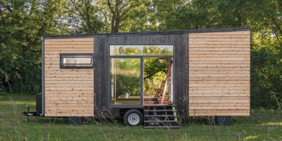 """<p>The sleek design by New Frontier Tiny Homes features a <a href=""""http://www.homedepot.com/p/KOHLER-Whitehaven-Undermount-Farmhouse-Apron-Front-Cast-Iron-36-in-Single-Basin-Kitchen-Sink-in-White-K-RH6489-0/205937235"""" rel=""""nofollow noopener"""" target=""""_blank"""" data-ylk=""""slk:farmhouse sink"""" class=""""link rapid-noclick-resp"""">farmhouse sink</a>, <a href=""""http://www.homedepot.com/p/Timeline-Wood-11-32-in-x-5-5-in-x-47-5-in-Distressed-White-Wood-Panels-6-Pack-00955/205791513"""" rel=""""nofollow noopener"""" target=""""_blank"""" data-ylk=""""slk:shiplap"""" class=""""link rapid-noclick-resp"""">shiplap</a> <em>and </em><a href=""""http://www.homedepot.com/p/Merola-Tile-Metro-Subway-Glossy-White-11-3-4-in-x-11-3-4-in-x-5-mm-Porcelain-Mosaic-Tile-9-6-sq-ft-case-FXLMSSW/100649499"""" rel=""""nofollow noopener"""" target=""""_blank"""" data-ylk=""""slk:subway tile"""" class=""""link rapid-noclick-resp"""">subway tile</a> squeezed into 200 square feet. Best of all, though, a sliding glass garage door reveals a deck that pops out from the home, making al fresco dining a cinch. </p><p><a class=""""link rapid-noclick-resp"""" href=""""https://www.countryliving.com/home-design/decorating-ideas/news/g3549/alpha-tiny-home/"""" rel=""""nofollow noopener"""" target=""""_blank"""" data-ylk=""""slk:SEE INSIDE"""">SEE INSIDE</a></p>"""