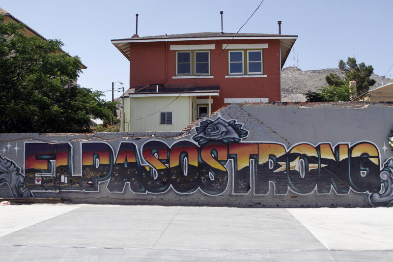 """This May 7, 2020 photo shows an """"El Paso Strong"""" mural painted in the wake of the Aug. 3, 2019 shooting by artists Gabe Vasquez and Justin Martinez in El Paso, Texas. The star painted in the mural's letters can be seen at night in the Franklin Mountains in the background.(AP Photo/Cedar Attanasio)"""