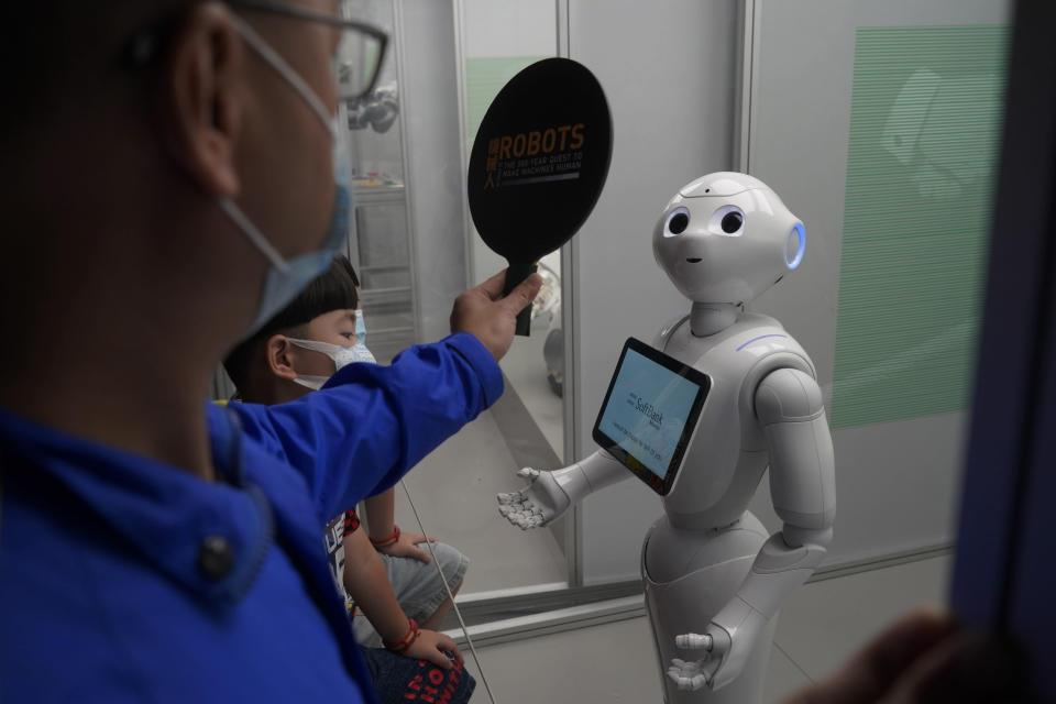"""French robot """"Pepper the droid"""" looks at the signal from a staff member at the exhibition """"Robots – The 500-Year Quest to Make Machines Human"""" in the Hong Kong Science Museum, Wednesday, May 19, 2021. (AP Photo/Kin Cheung)"""