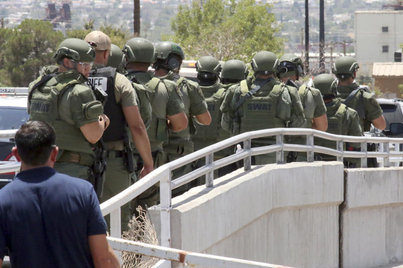 Law enforcement officers make their way along a walkway to the scene of a shooting at a shopping mall in El Paso, Texas, on Saturday, Aug. 3, 2019.   Several people were killed in the shooting Saturday in a busy shopping area in the Texas border town.  (AP Photo/Rudy Gutierrez)