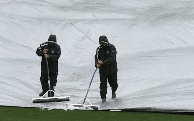 Workers remove water from a tarp covering the field prior to an exhibition baseball game between the San Francisco Giants and the Oakland Athletics Saturday, March 29, 2014, in Oakland, Calif. (AP Photo/Ben Margot)