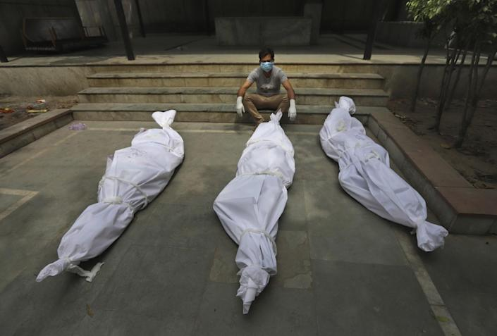 A man sits beside wrapped bodies