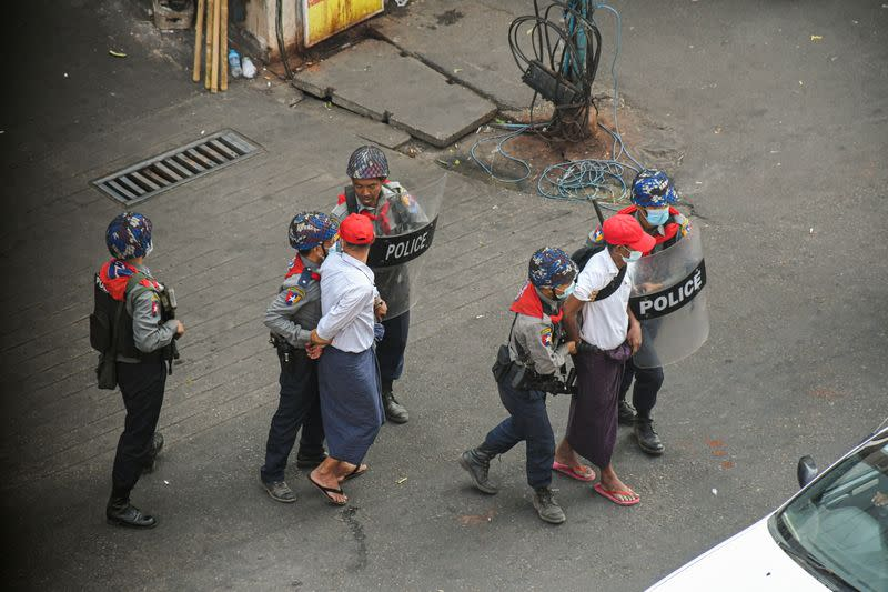 Anti-coup demonstrators are detained by police officers during a protest against the military coup in Yangon