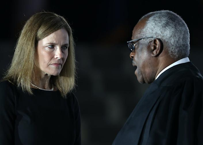 Judge Amy Coney Barrett talks with Supreme Court Associate Justice Clarence Thomas during her ceremonial swearing-in ceremony to be U.S. Supreme Court.