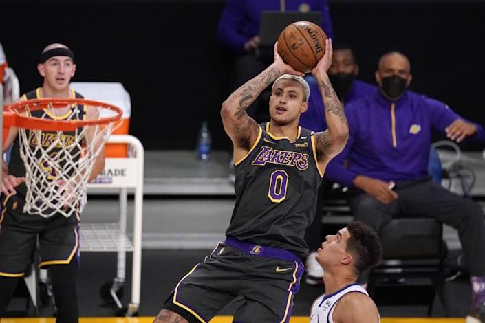 Los Angeles Lakers forward Kyle Kuzma, center, shoots as Denver Nuggets forward Michael Porter Jr., right, defends and guard Alex Caruso watches during the first half of an NBA basketball game Monday, May 3, 2021, in Los Angeles. (AP Photo/Mark J. Terrill)